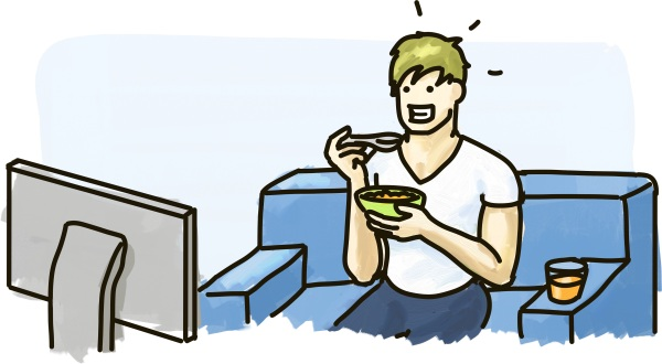 A man looks very happy while eating his breakfast in front of the television.